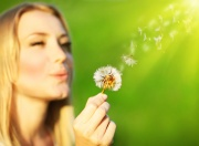 Happy beautiful girl blowing dandelion